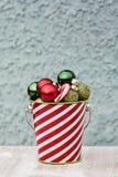 Bolas pequenas festivas recolhidas em cubeta listrada para o Natal Fotografia de Stock