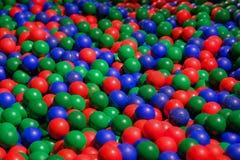 Bolas plásticas del color en patio de los niños Imagenes de archivo