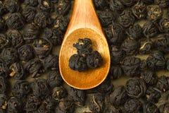 Bolas pretas chinesas da folha de chá dentro da colher de madeira Fotografia de Stock