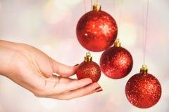 Bolas redondas rojas de la Navidad y mano femenina Foto de archivo