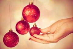 Bolas redondas rojas de la Navidad y mano femenina Foto de archivo libre de regalías
