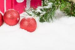 Bolas rojas con la actual caja en nieve Fotos de archivo libres de regalías