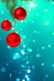 Bolas rojas de la Navidad con el árbol de abeto verde en bokeh azul colorido Foto de archivo