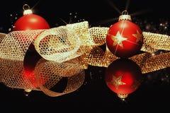 Bolas rojas de la Navidad con la cinta de oro del metal Foto de archivo libre de regalías