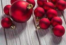 Bolas rojas de la Navidad en los tableros de madera blancos Imagenes de archivo