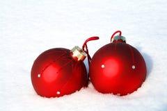 Bolas rojas de la Navidad en nieve Imágenes de archivo libres de regalías