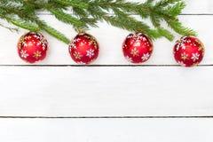 Bolas rojas de la Navidad en una rama verde en un backgrou de madera blanco imágenes de archivo libres de regalías