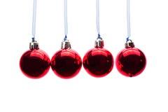 Bolas rojas de la Navidad que cuelgan en fila en el fondo blanco Fotos de archivo libres de regalías