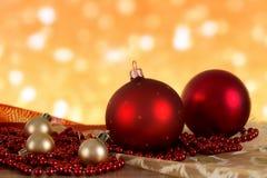 Bolas rojas de la Navidad y gotas de oro en un fondo borroso Fotografía de archivo libre de regalías