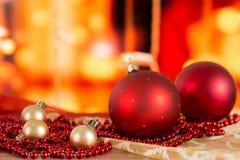 Bolas rojas de la Navidad y gotas de oro en un fondo borroso Foto de archivo libre de regalías