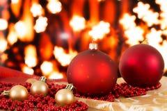 Bolas rojas de la Navidad y gotas de oro en un fondo borroso Imagen de archivo