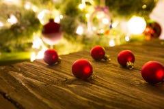 Bolas rojas de las decoraciones del árbol de navidad que ponen en una tabla de madera rústica lista para ser colgado en un árbol  Imagen de archivo libre de regalías