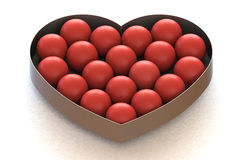 Bolas rojas en caja en forma de corazón del metal Imágenes de archivo libres de regalías