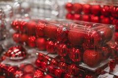 Bolas rojas en las cajas para las decoraciones de la Navidad en un escaparate de la tienda imagen de archivo