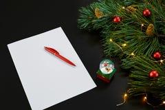 Bolas rojas y cuaderno de la Navidad que mienten cerca de rama spruce verde en la opinión superior del fondo negro Espacio para e Imagen de archivo