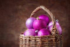 Bolas rosadas brillantes de la Navidad en una cesta Fotografía de archivo libre de regalías