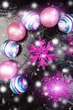 Bolas rosadas y púrpuras de la Navidad y copos de nieve decorativos en fondo negro Endecha plana Foto de archivo