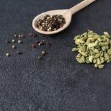 Bolas verdes das vagens do cardamomo e das pimentas da mistura na colher de madeira Fotografia de Stock Royalty Free