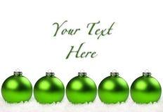 Bolas verdes de la Navidad alineadas en la nieve Fotografía de archivo libre de regalías