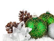 Bolas verdes en nieve con el arqueamiento del oro Imagenes de archivo