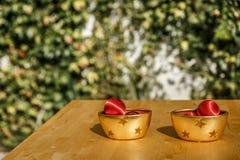 Bolas vermelhas do Natal sobre bacias amarelas em uma tabela de madeira Foto de Stock Royalty Free