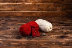 Bolas vermelhas e brancas de agulhas da linha e de confecção de malhas em um fundo de madeira fotografia de stock royalty free