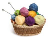 Bolas y agujas del hilo para obras de punto en cesta Fotografía de archivo libre de regalías
