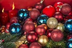 Bolas y candels de la decoración de la Navidad y del Año Nuevo en fondo rojo fotos de archivo libres de regalías