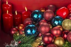 Bolas y candels de la decoración de la Navidad y del Año Nuevo en fondo rojo foto de archivo