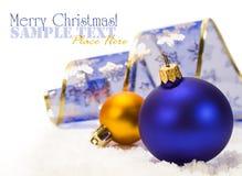 Bolas y cinta de la Navidad del azul y del oro en nieve Fotografía de archivo