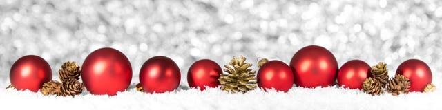 Bolas y conos rojos de la Navidad en la nieve, fondo del brillo Imágenes de archivo libres de regalías