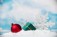Bolas y copos de nieve de la Navidad en nieve en el cielo del fondo Fotos de archivo libres de regalías