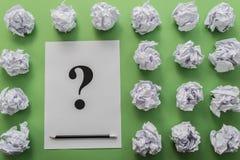 Bolas y hoja de papel de papel arrugadas con la pregunta-marca Imágenes de archivo libres de regalías