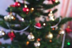 Bolas y juguetes brillantes rojos del oro en las ramas del árbol de navidad Guirnalda de la Navidad con las luces en el árbol de  imagen de archivo libre de regalías
