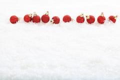 Bolas y nieve de la Navidad en el fondo blanco Imágenes de archivo libres de regalías
