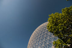 Bold blue sky and biosphere. The Montreal biosphere is foregrounded by the vast blue sky, contrasted against the verdant green of a tree royalty free stock images