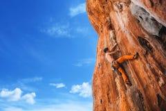 Bold choice - rock climbing. Rebellious rock climber on the wall - bold choice of real men. Stock Image Stock Photography