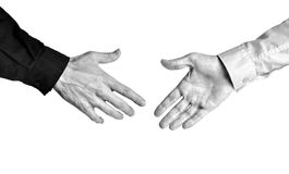 Bold contrast black and white of businessmen showing trust in a deal with a handshake. High contrast black and white photo of two businessmen reaching for a Royalty Free Stock Photos