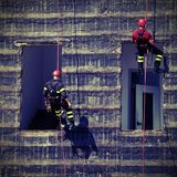 Climbers of firefighters climbing a wall. Bold and daring climbers of firefighters climbing a wall of a house stock images