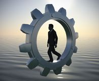 Bold Executive manager walking inside a metallic gear at sea since dawn. An executive walking inside a gear at sea since dawn demonstrating hard work and Stock Image