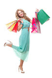 Bold girl holding shopping bags. Smiling beautiful young girl with blond curly hair on high heels in summer dress holding shopping bags royalty free stock photo