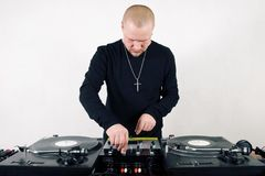 Bold hip-hop DJ mixing vinyl. Young adult white guy playing music from turntables Stock Photo