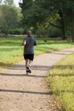 Bold man jogging in the park. Bold muscular wet man jogging in the park in sunset lights stock photography