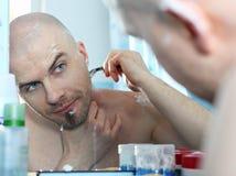 Bold man shaving. Man shaving his head in the bathroom Royalty Free Stock Photo