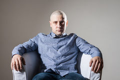 Bold man sitting in a chair. Bold man sit in a chair royalty free stock photography