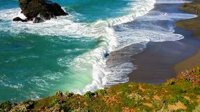 Bold Palate &Colors of the Sea. Strong and forceful nature. Sandy beach with rust colored A strong and bold foreground of vegetation in rust, gold, green and royalty free stock photography