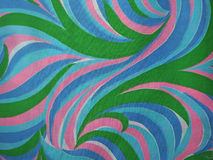 Bold 1970's Pink Blue and Green Swirling Mod Design. Swirling 1970's mod pattern on fabric with green, light and darker blues, pink and a little white stock photo