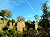 Bole Hill Quarry, Derbyshire. Grindleford, Derbyshire, UK. September 29, 2016.  The overgrown gritstone rock face of the old Bole Hill quarry with rock climbers Royalty Free Stock Image