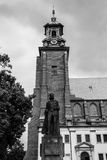 Boleslaw Chrobry Statue with Gniezno Cathedral Tower Clock. POLAND, GNIEZNO - 29 JUNE 2015: Boleslaw Chrobry Statue with Gniezno Cathedral Tower Clock, black and Royalty Free Stock Photos