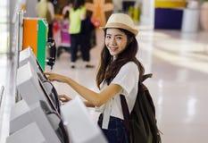 Boleto asiático de la reservación de la mujer del adolescente en el aeropuerto Imagen de archivo